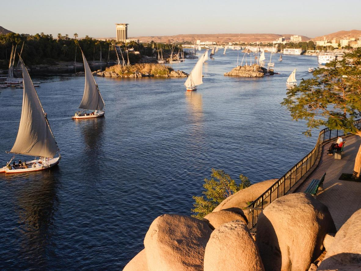 Sailboats glide past the ancient city of Elepahantine along the wide, palm-lined Nile River