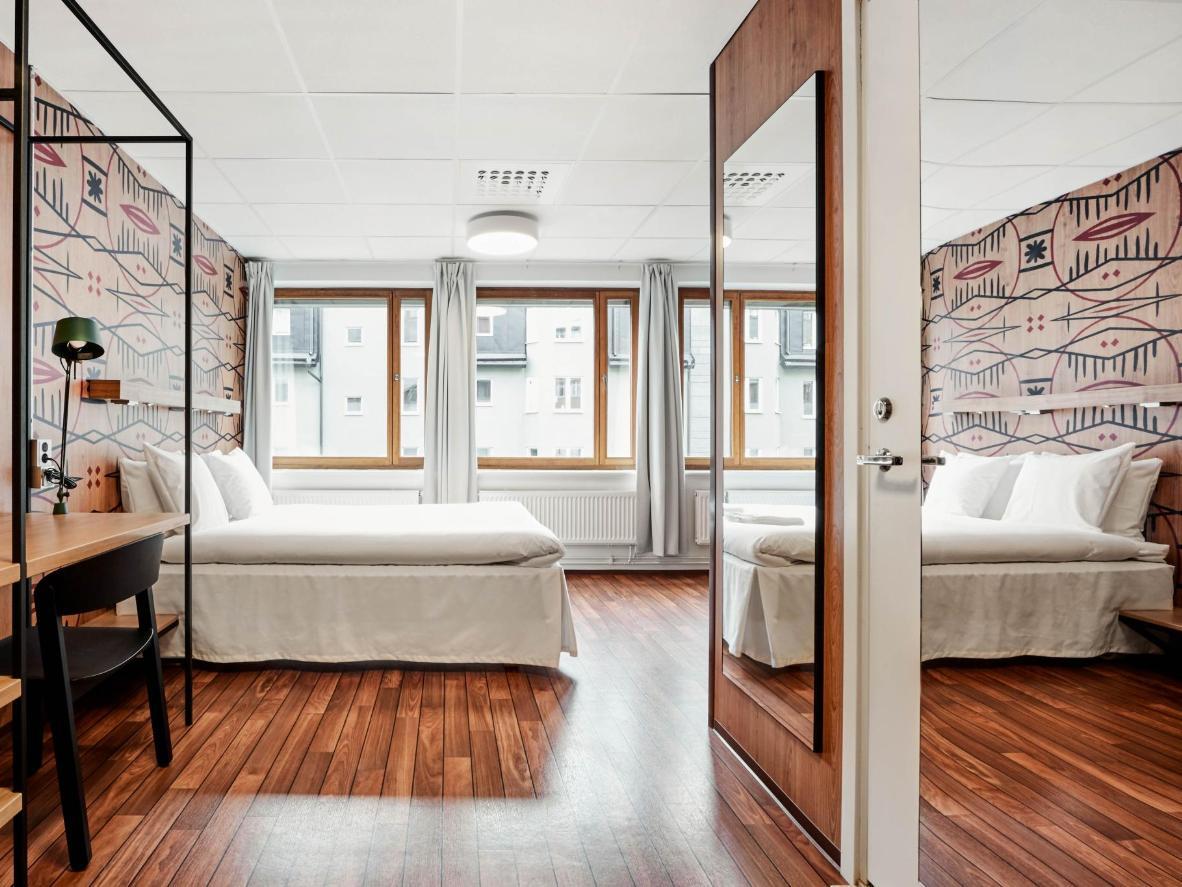 Polished wooden floorboards and crisp white linen at Generator Stockholm