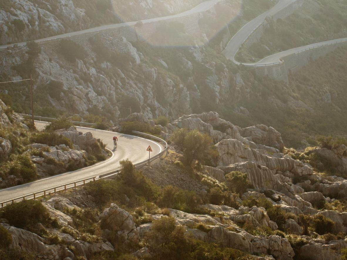 Een eenzame fietser onderweg naar de top van de bochtige en uitdagende Sa Calobra op Mallorca