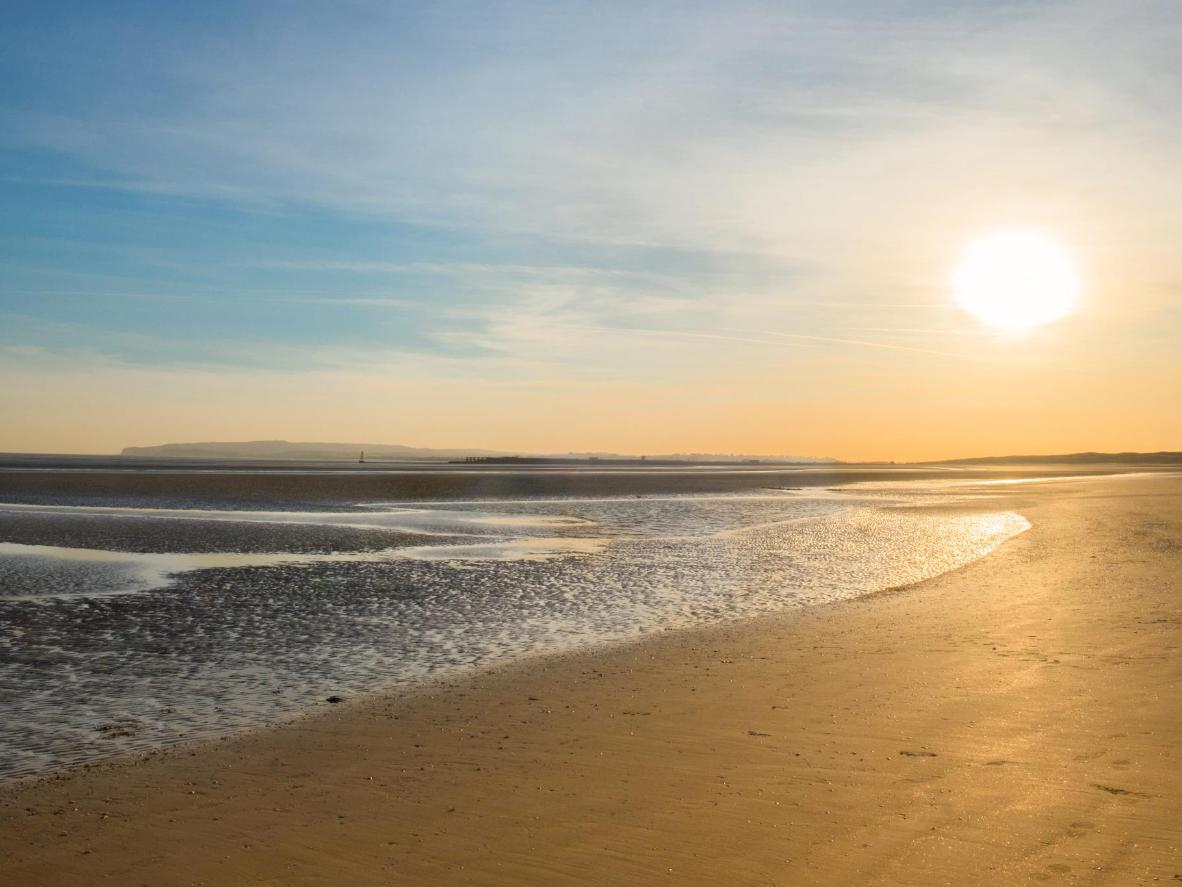 Walk along the wide beach at Camber and watch sunset rays glinting off the sea