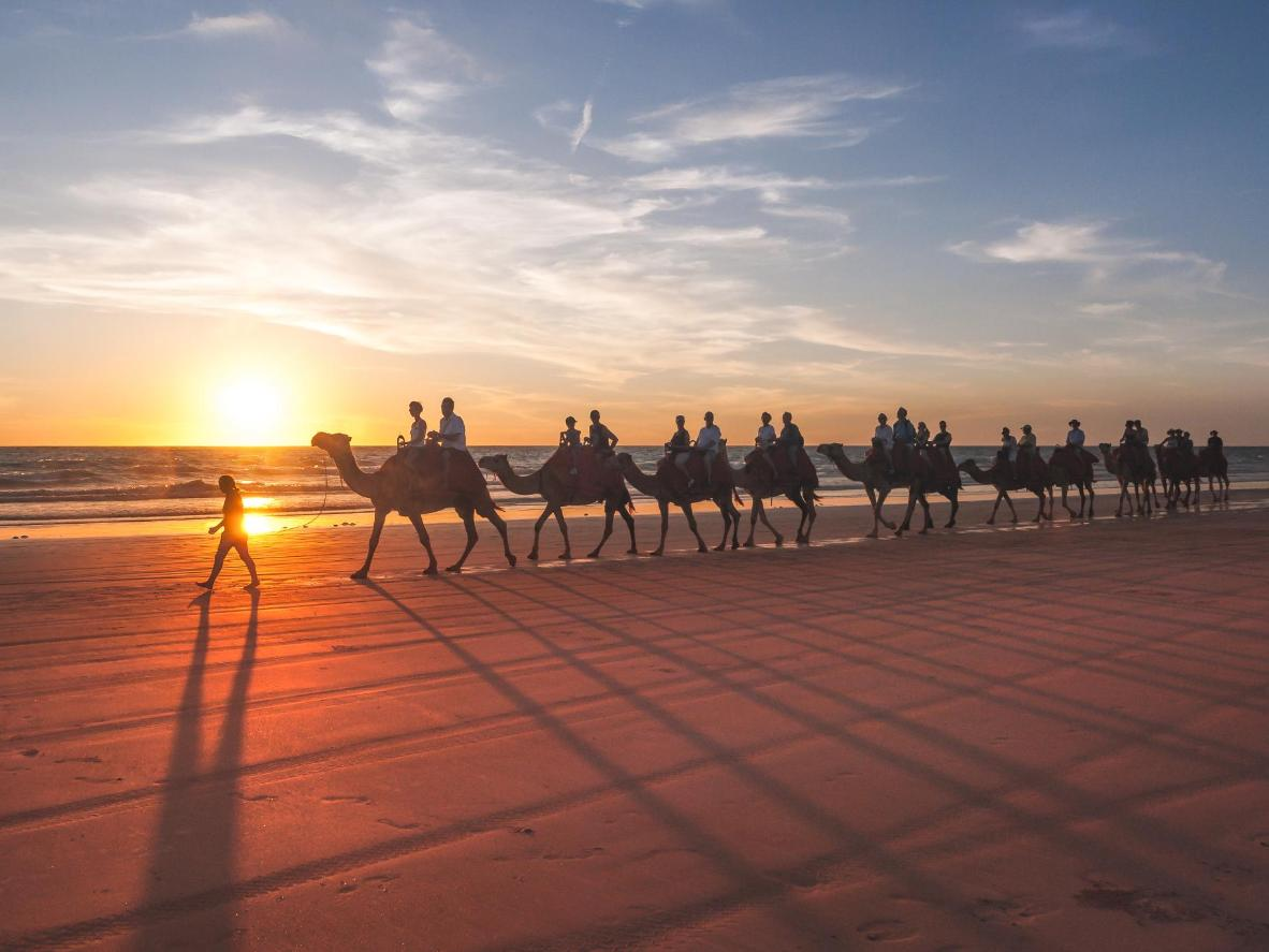 Hopping on the back of a camel for a ride along the sand is a popular way to see the sunset on Broome's 22km-long Cable Beach
