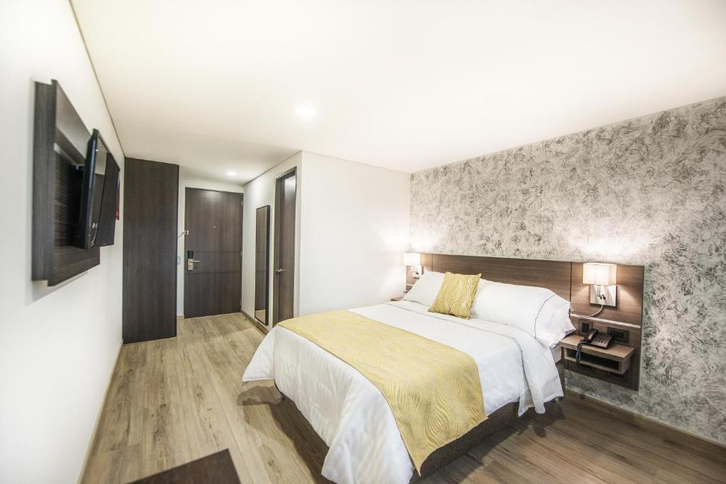 A bed or beds in a room at Hotel Grand Plaza Corferias