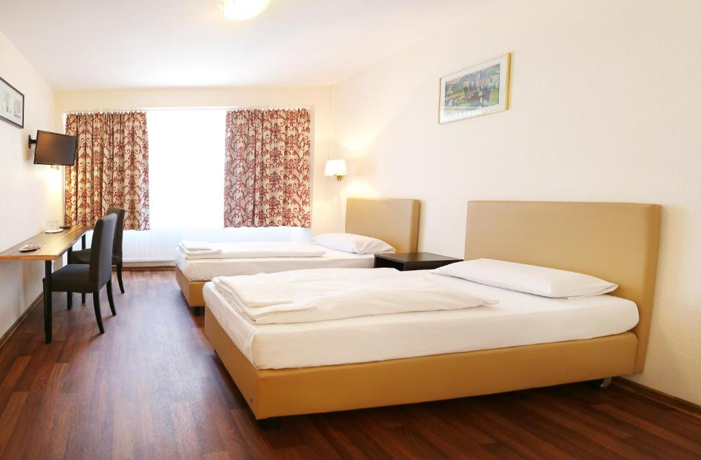 A bed or beds in a room at Pension Alpha Frankfurt City