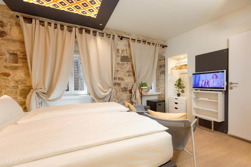 A bed or beds in a room at Luxury Rooms Bajamonti