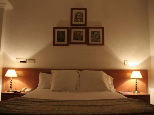 A bed or beds in a room at Hostal Gran Via Levante
