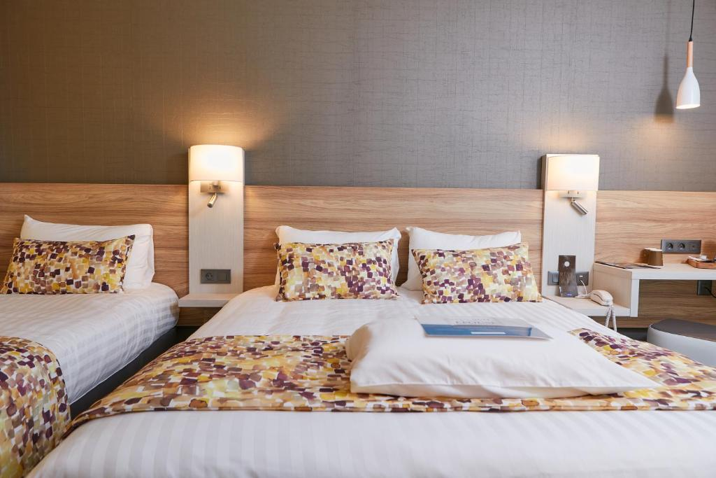 A bed or beds in a room at Kyriad Pontarlier
