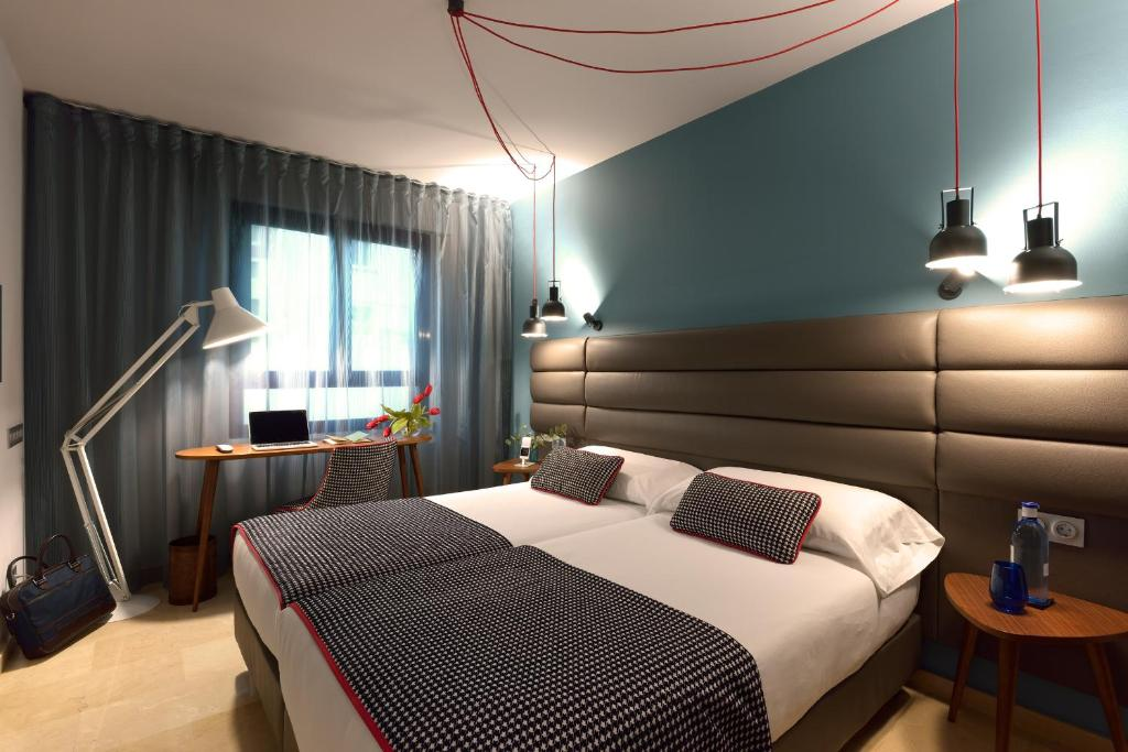 A bed or beds in a room at Hotel Pamplona Plaza
