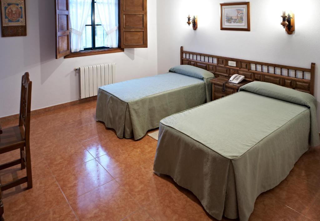 A bed or beds in a room at Hospederia Monasterio de Poio