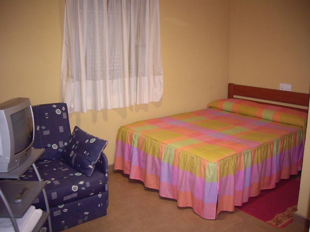A bed or beds in a room at Pensión la Estación