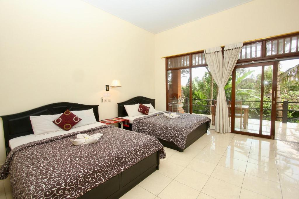A bed or beds in a room at Rahayu House Ubud