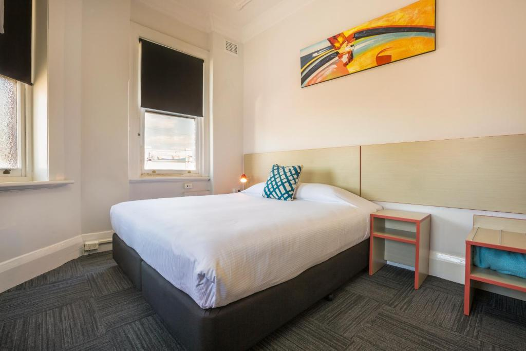 A bed or beds in a room at Melton Hotel Auburn