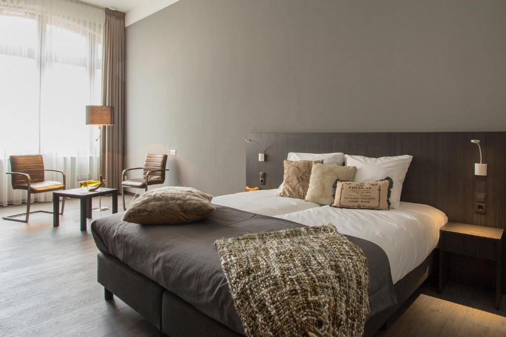 A bed or beds in a room at Hotel Bladel
