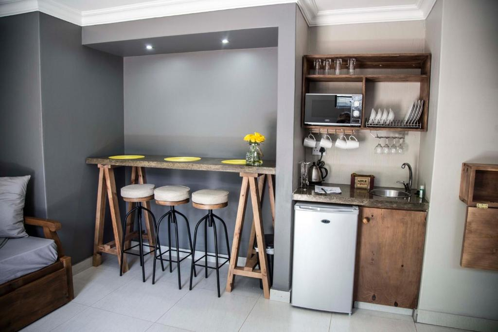 A kitchen or kitchenette at Touching senses Garden Cottages