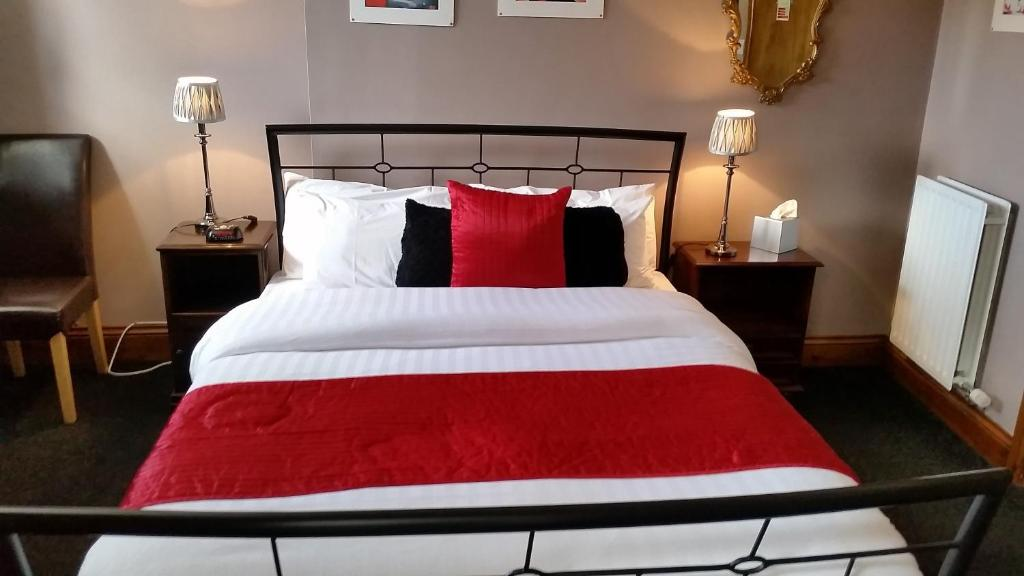 A bed or beds in a room at Forresters Hotel, Bar & French Restaurant
