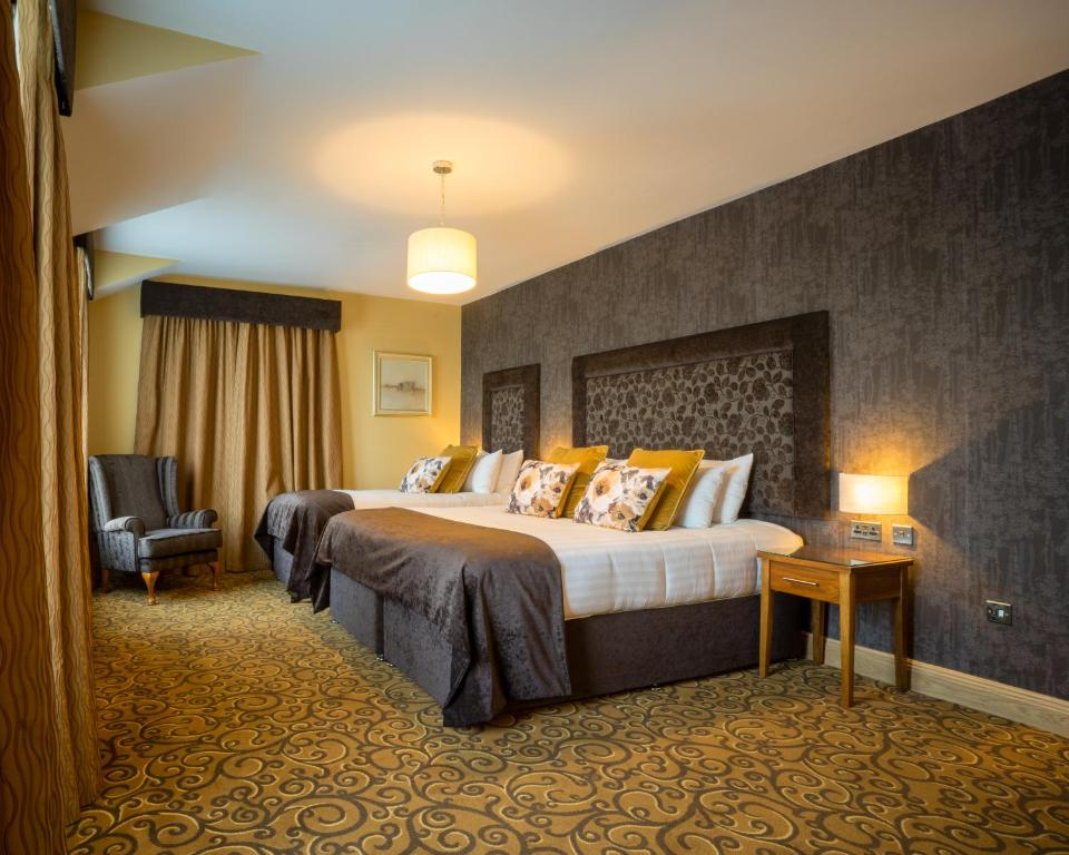 A bed or beds in a room at Kettles Country House Hotel