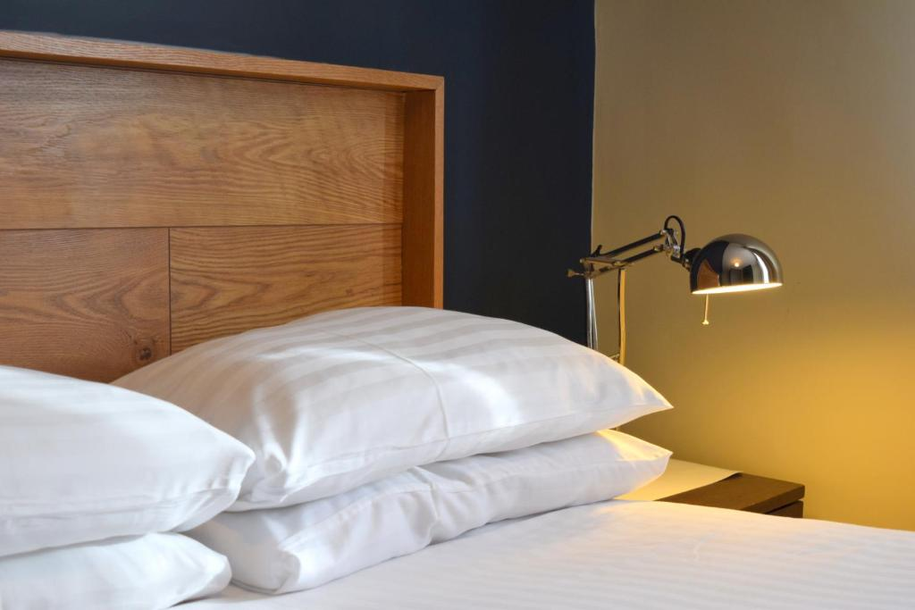 A bed or beds in a room at Griffin House Hotel