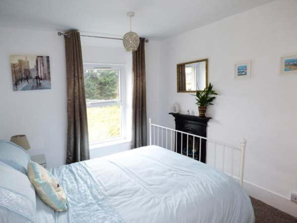 A bed or beds in a room at Y Ddraig Deg