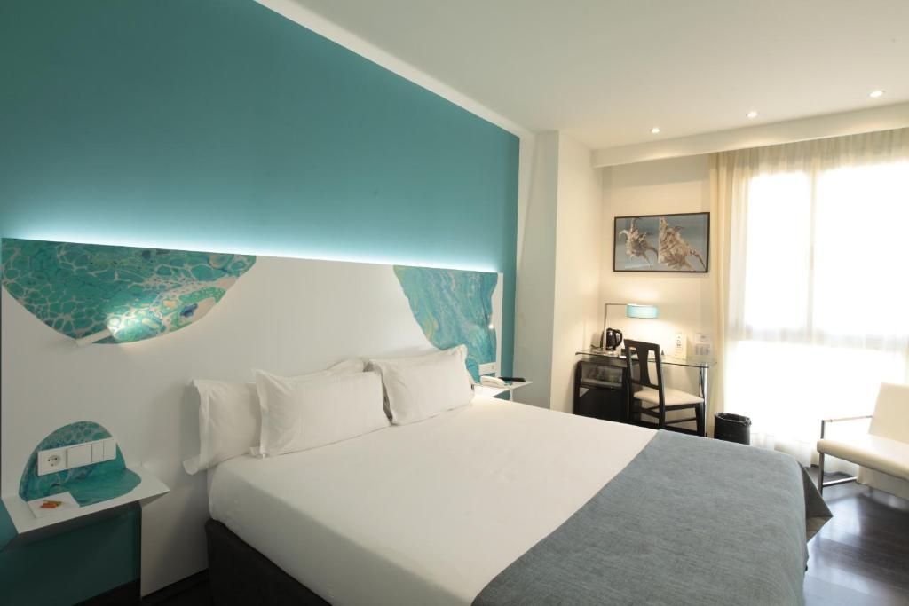 A bed or beds in a room at Hotel Concordia Barcelona