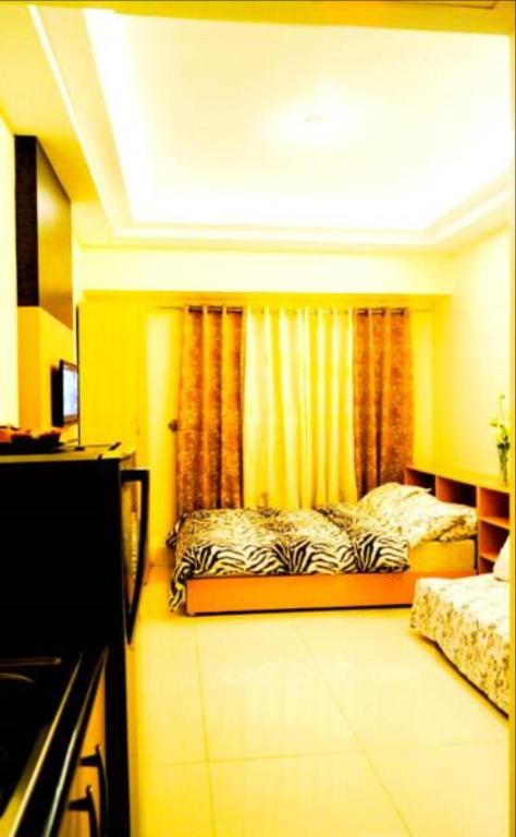 A bed or beds in a room at JT Suites Tagaytay @ SMDC Wind Residences