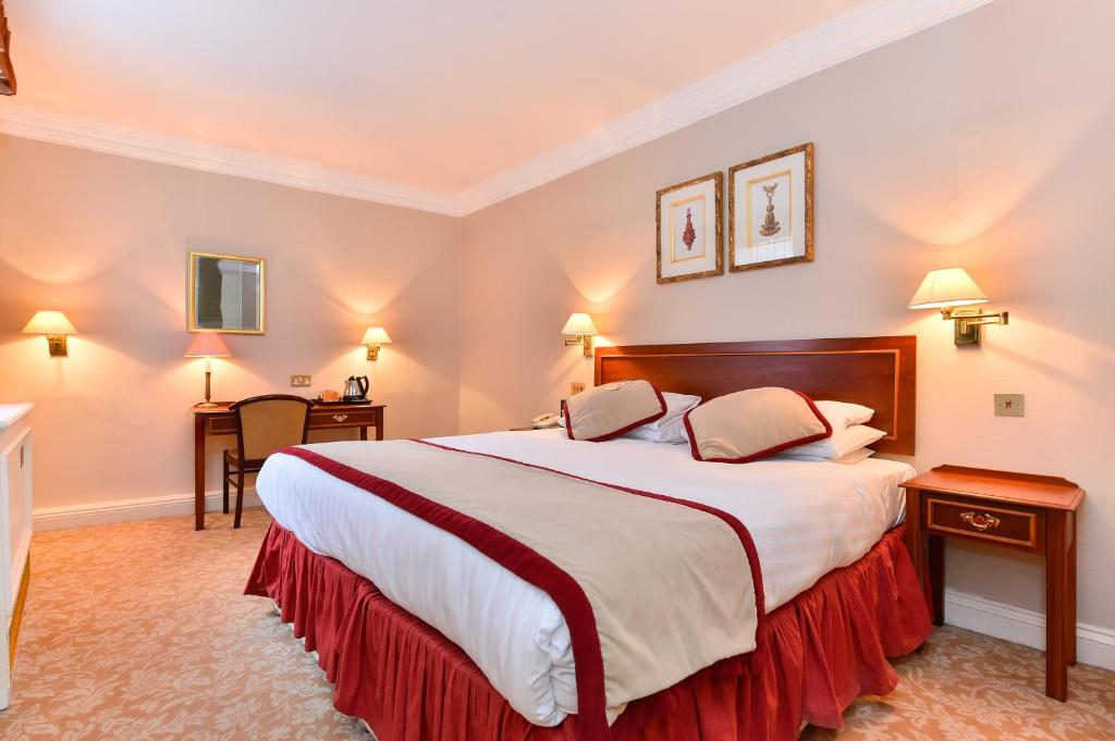 A bed or beds in a room at Park Lane Mews Hotel
