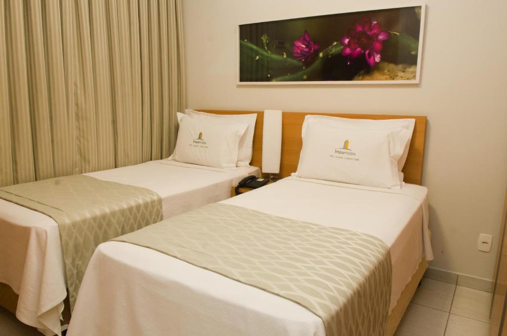 A bed or beds in a room at Ímpar Suítes Cidade Nova