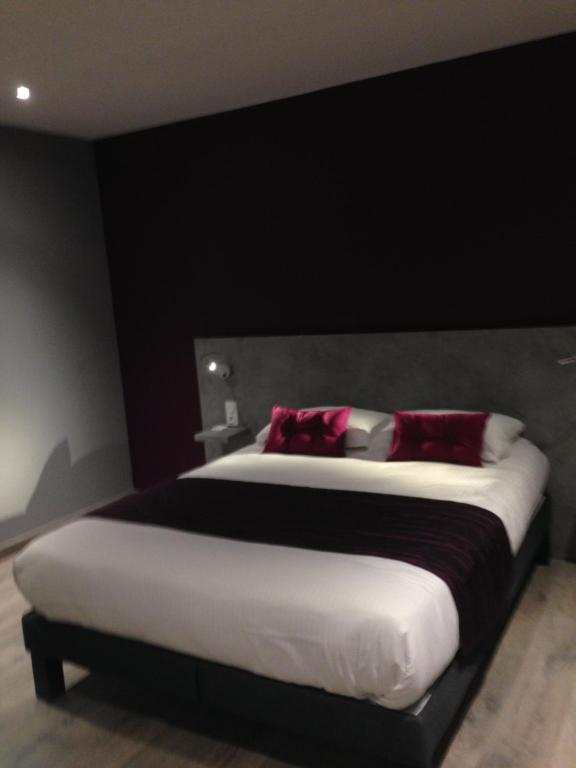 A bed or beds in a room at Logis La Fontaine