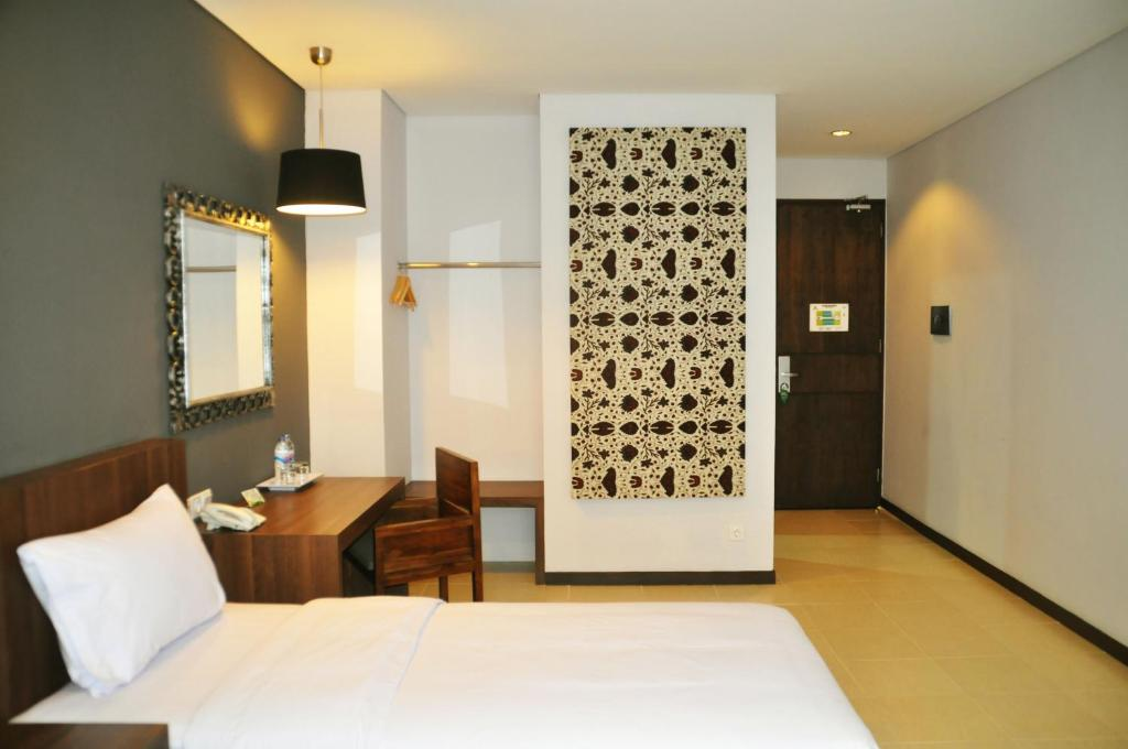 A bed or beds in a room at Praja Hotel