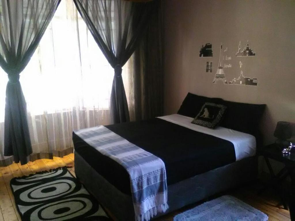 A bed or beds in a room at Rosegarden guest house