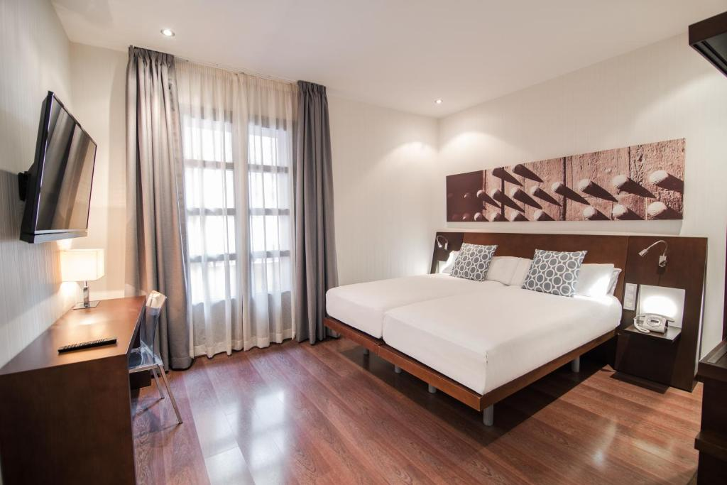 A bed or beds in a room at Petit Palace Marques Santa Ana