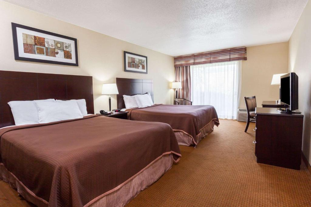 A bed or beds in a room at Toronto East Inn