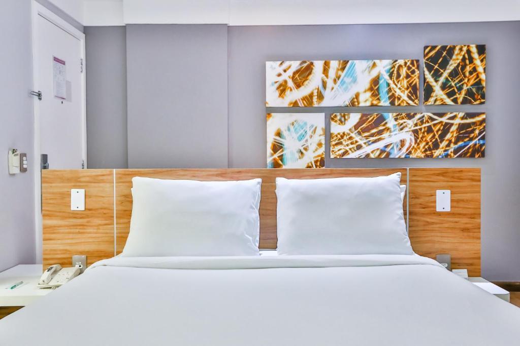 A bed or beds in a room at Quality Suítes Rio de Janeiro Botafogo