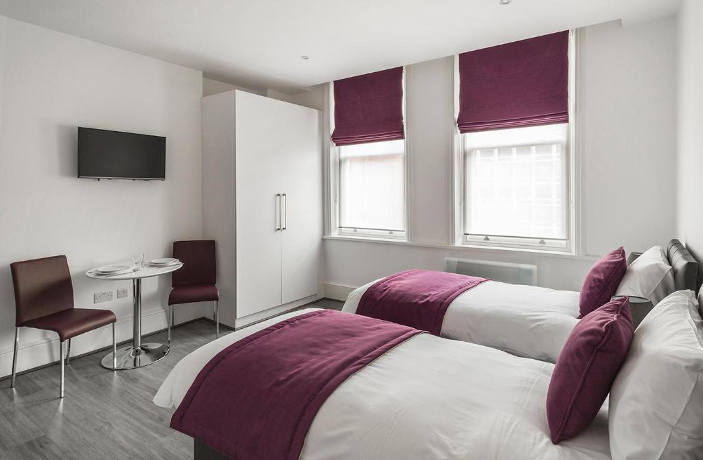 A bed or beds in a room at Smart Stay Swiss Cottage