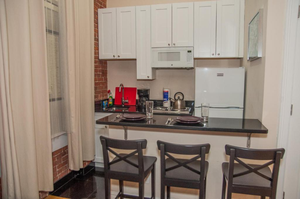 A kitchen or kitchenette at New York Apartments