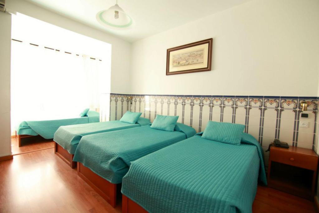 A bed or beds in a room at Residencial Joao XXI