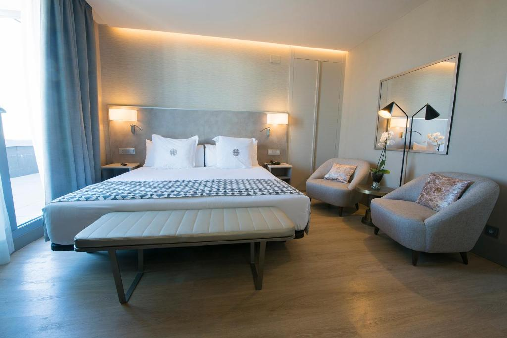 A bed or beds in a room at Hotel América Sevilla