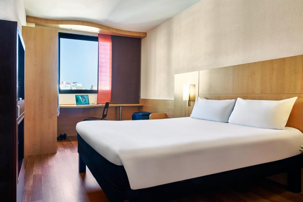 A bed or beds in a room at Ibis Barcelona Centro (Sagrada Familia)