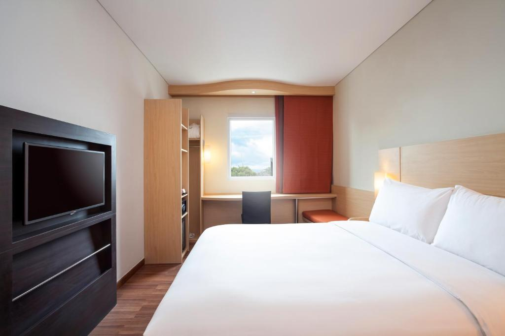 A bed or beds in a room at Ibis Makassar City Center