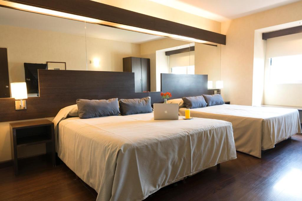 A bed or beds in a room at Hathor Hotels Mendoza