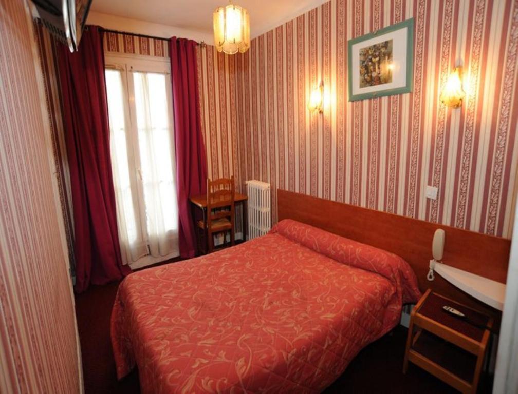 Ein Bett oder Betten in einem Zimmer der Unterkunft Sully Hôtel