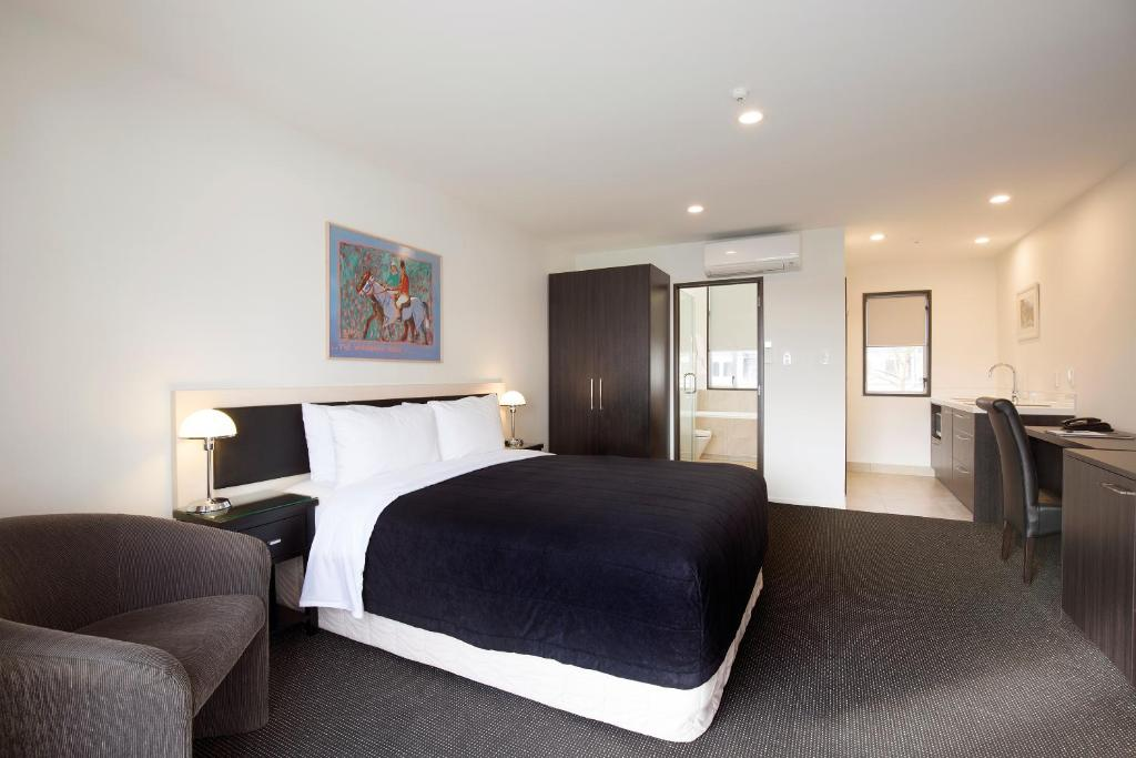 A bed or beds in a room at Pavilions Hotel