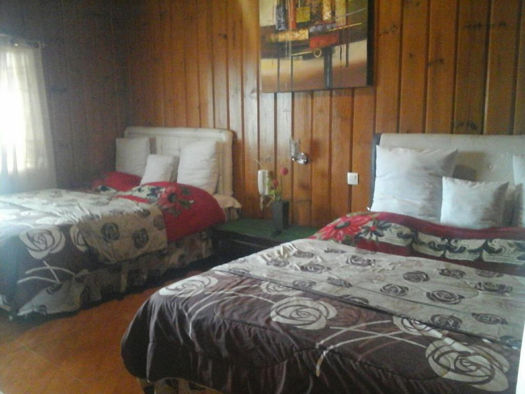 A bed or beds in a room at Cemara Indah Hotel