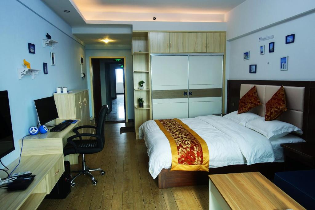 A bed or beds in a room at Fengyuan Apartment Hotel