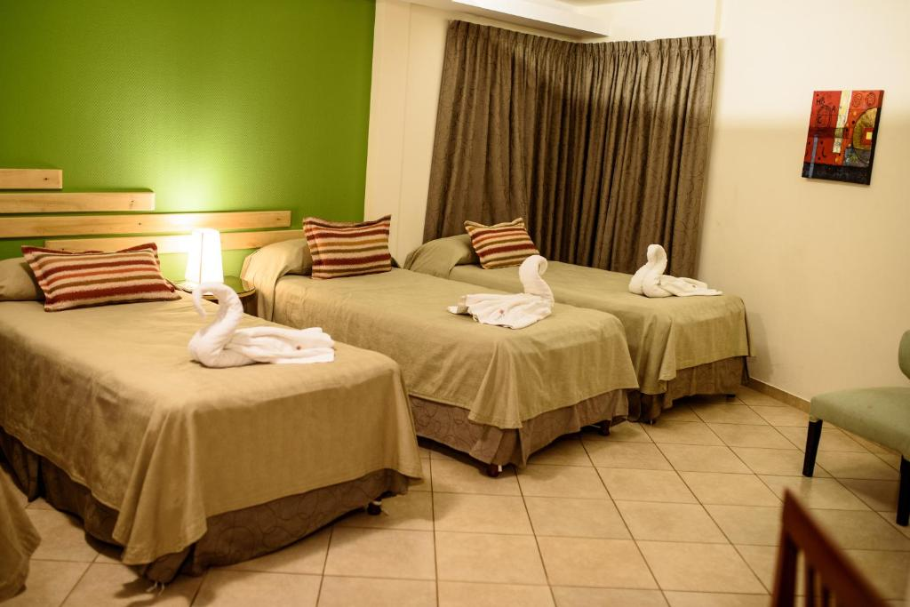 A bed or beds in a room at AVEMAR Apart Hotel