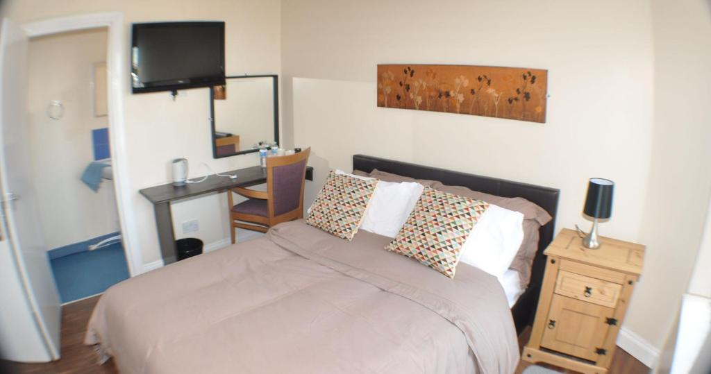 A bed or beds in a room at The Olive Lodge