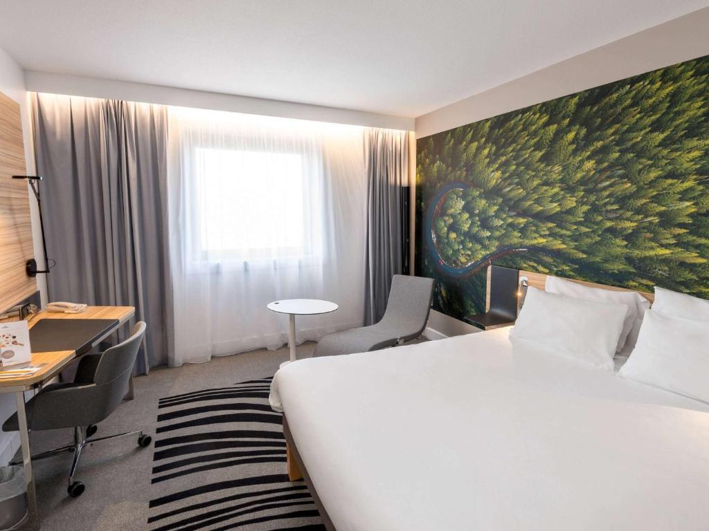 Een bed of bedden in een kamer bij Novotel Marne La Vallee Noisy Le Grand