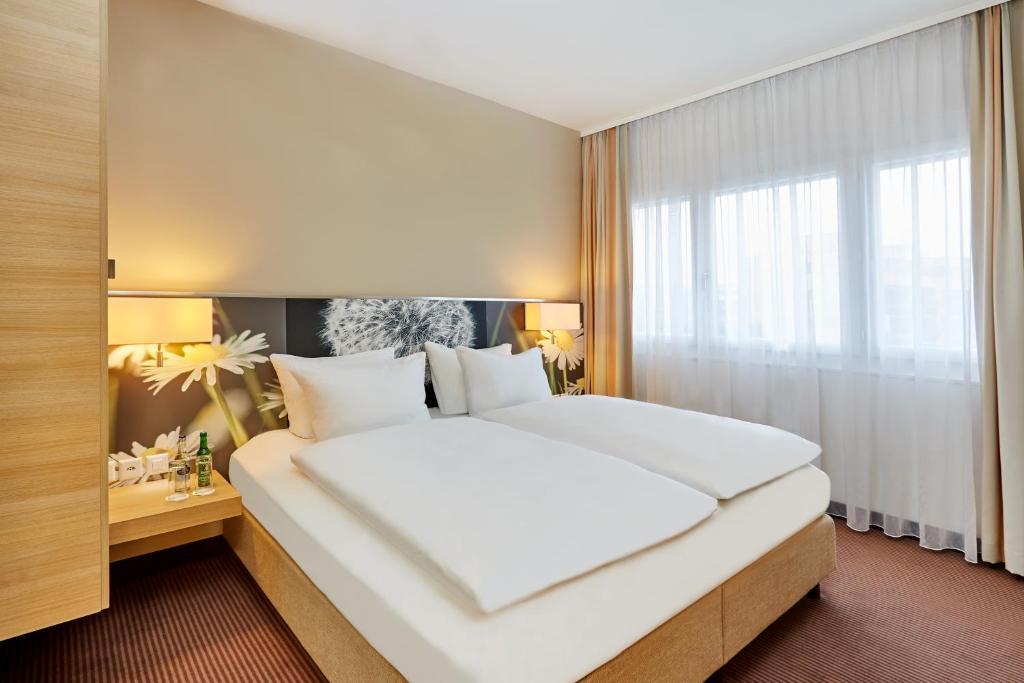 Uma cama ou camas num quarto em H+ Hotel Zürich