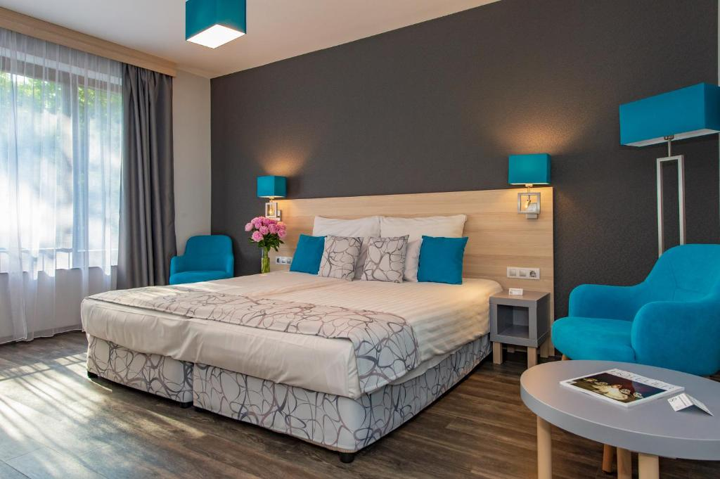 A bed or beds in a room at Hotel Regnum Residence