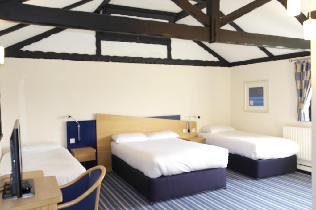A bed or beds in a room at Beadlow Manor Hotel