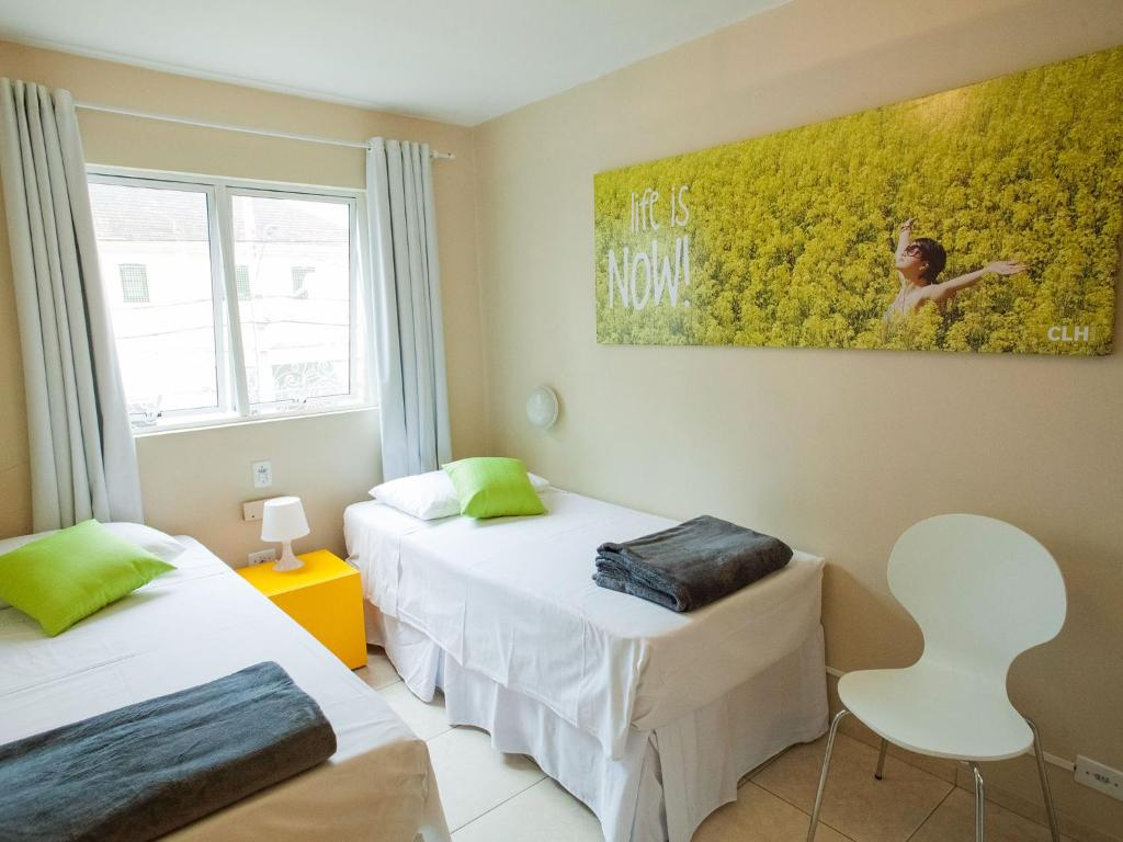 A bed or beds in a room at CLH Suites Curitiba