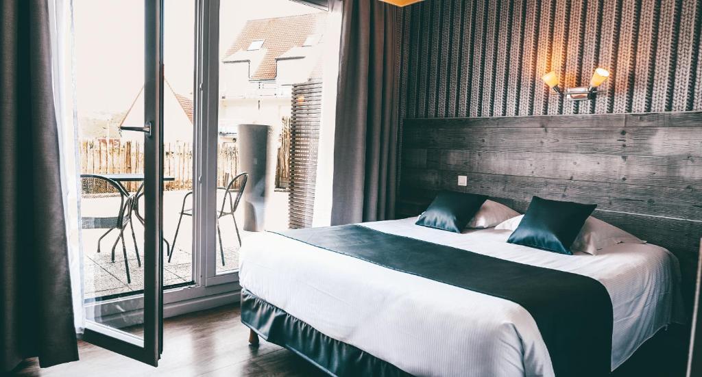 A bed or beds in a room at Hôtel de la Baie de Wissant Sauna Hammam